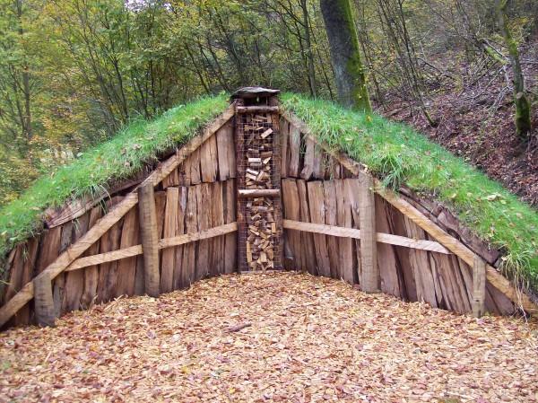 Ein Schaumeiler, der auch zum Waldarbeiter und Försterpfad gehört, aufgeschichtetes Buchenholz, der Kamin zum Anzündung und die Abdeckung  mit Erde und Gras